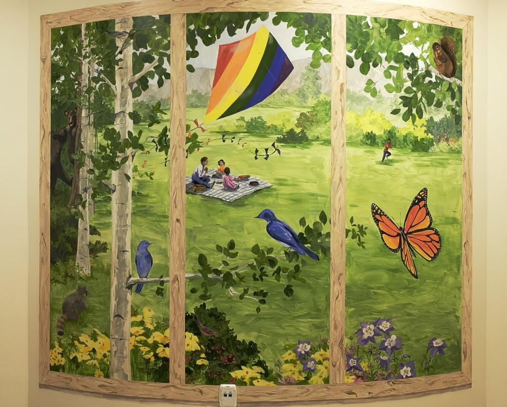 hand painted mural in Boulder Community Health Pediatric playroom  by Boulder Murals bears, humming birds, butterflies, kites, picnic